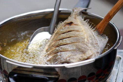 Khi dầu sôi thì cho cá vào chiên